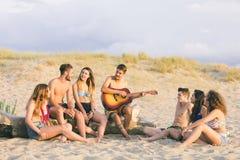 Grupo de amigos que cantan en la playa en la puesta del sol Fotos de archivo libres de regalías