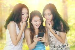 Grupo de amigos que charlan con smartphone Imagenes de archivo