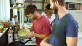 Grupo de amigos que cocinan el desayuno en cocina junto almacen de video