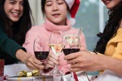 Grupo de amigos que comemoram o Natal em casa e o brinde dos tampões Fotografia de Stock