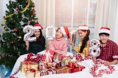 Grupo de amigos que comemoram o Natal em casa e que mostram 2018 acima Foto de Stock Royalty Free