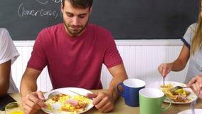 Grupo de amigos que comen el desayuno cocinado en cocina junto almacen de video