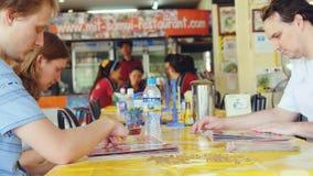 Grupo de amigos que comen la comida tailandesa en café de la calle Fotos de archivo