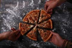 Grupo de amigos que comen la pizza Imagen de archivo