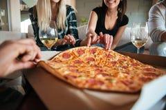 Grupo de amigos que comen la pizza grande y la consumición Imágenes de archivo libres de regalías