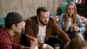 Grupo de amigos que comen la pizza que habla y que ríe en un café almacen de metraje de vídeo