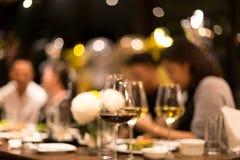 Grupo de amigos que comen una cena y un vino en conceptaul borroso imagenes de archivo
