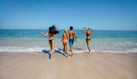 Grupo de amigos que correm na água do mar foto de stock royalty free