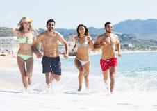 Grupo de amigos que corren en la arena en la playa Imagen de archivo