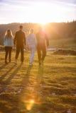Grupo de amigos que corren feliz junto en la hierba y el salto Imágenes de archivo libres de regalías