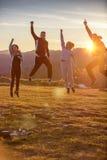 Grupo de amigos que corren feliz junto en la hierba y el salto Imagen de archivo