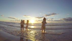 Grupo de amigos que corren hacia el mar en la playa hermosa en la salida del sol almacen de metraje de vídeo
