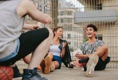 Grupo de amigos que cuelgan hacia fuera en la cancha de básquet Fotografía de archivo libre de regalías