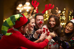 Grupo de amigos que disfrutan de bebidas de la Navidad en barra Fotos de archivo