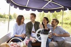 Grupo de amigos que disfrutan de día hacia fuera en barco en el río junto imagenes de archivo