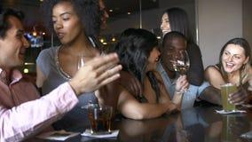 Grupo de amigos que disfrutan de la bebida en la barra junto almacen de video