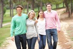 Grupo de amigos que disfrutan de la caminata en parque Imagen de archivo