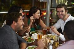 Grupo de amigos que disfrutan de la cena en restaurante imagenes de archivo