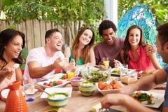 Grupo de amigos que disfrutan de la comida al aire libre en casa imagenes de archivo