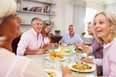 Grupo de amigos que disfrutan de la comida en casa junto foto de archivo libre de regalías