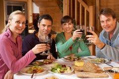 Grupo de amigos que disfrutan de la comida en chalet alpestre fotos de archivo