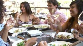 Grupo de amigos que disfrutan de la comida en el restaurante al aire libre almacen de metraje de vídeo
