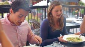 Grupo de amigos que disfrutan de la comida en el restaurante al aire libre almacen de video