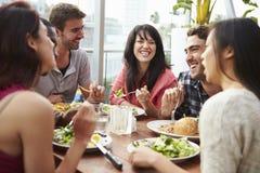 Grupo de amigos que disfrutan de la comida en el restaurante del tejado fotos de archivo