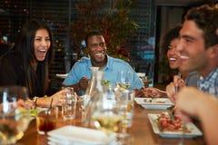 Grupo de amigos que disfrutan de la comida en restaurante Foto de archivo