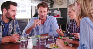 Grupo de amigos que disfrutan de la comida en restaurante junto almacen de video