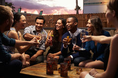 Grupo de amigos que disfrutan de noche hacia fuera en la barra del tejado Foto de archivo