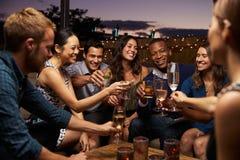 Grupo de amigos que disfrutan de noche hacia fuera en la barra del tejado imagen de archivo