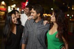 Grupo de amigos que disfrutan de noche hacia fuera junto Foto de archivo