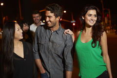 Grupo de amigos que disfrutan de noche hacia fuera junto Imagen de archivo