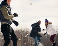 Grupo de amigos que disfrutan de una lucha de la bola de nieve en la nieve en invierno Imagen de archivo libre de regalías