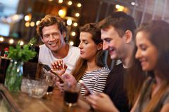 Grupo de amigos que disfrutan de la comida en restaurante imagen de archivo