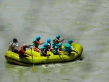 Grupo de amigos que disfrutan de transportar en balsa de río fotos de archivo