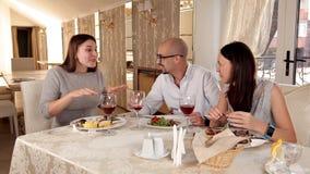 Grupo de amigos que disfrutan de una cena con el vino en un restaurante almacen de metraje de vídeo