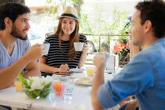 Grupo de amigos que encontram-se na cafetaria local fotos de stock royalty free
