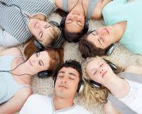 Grupo de amigos que escuchan la música en el suelo foto de archivo