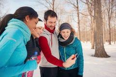 Grupo de amigos que escuchan la música en la nieve en invierno Fotografía de archivo