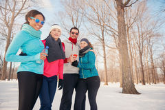 Grupo de amigos que escuchan la música en la nieve en invierno Fotos de archivo libres de regalías