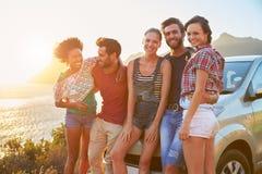 Grupo de amigos que estão pelo carro na estrada litoral no por do sol imagem de stock