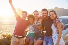 Grupo de amigos que estão pelo carro na estrada litoral no por do sol imagem de stock royalty free