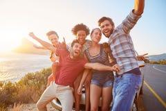 Grupo de amigos que estão pelo carro na estrada litoral no por do sol foto de stock royalty free