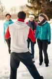 Grupo de amigos que estiran en la nieve en invierno Imágenes de archivo libres de regalías