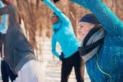 Grupo de amigos que estiran en la nieve en invierno Fotos de archivo libres de regalías