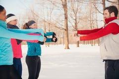 Grupo de amigos que estiran en la nieve en invierno Imagenes de archivo