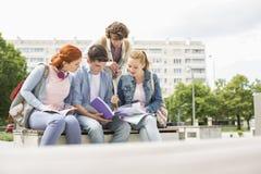 Grupo de amigos que estudian junto en campus universitario imagen de archivo libre de regalías