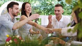 Grupo de amigos que fazem apostado agitando as mãos na reunião no café video estoque